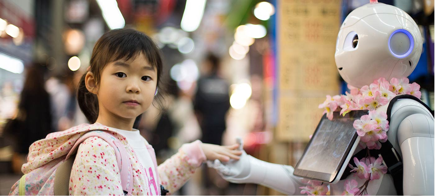 A young girl holds hands with a robot