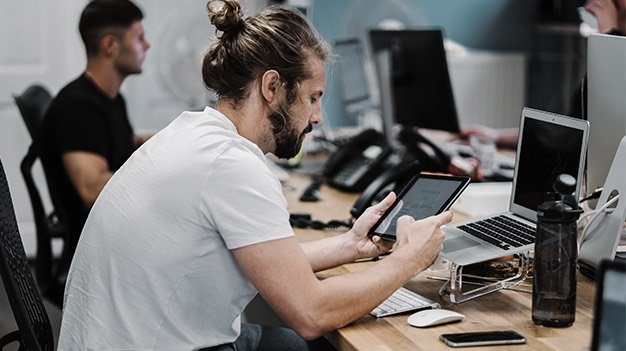 Man with man bun looking at tablet