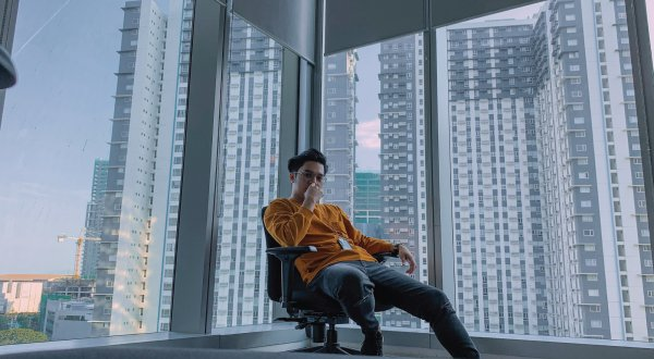 A person sits in a room in a high rise building surrounded by glass windows.