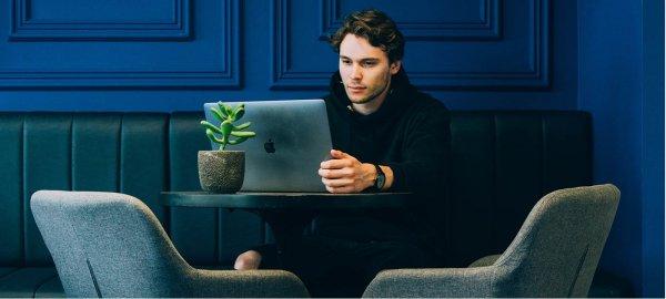 A man sits at a table looking at his laptop screen.