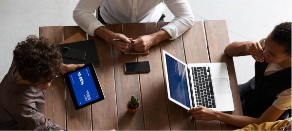 Three people sit around a table with tablets and laptops to discuss work