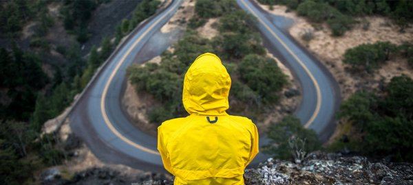 Someone in a yellow raincoat looks out over a valley with two paths to choose from