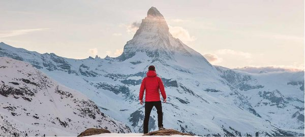 A person stands in the snowy wilderness gazing up at a mountain peak