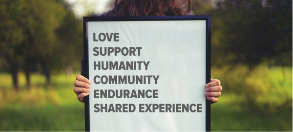 A person holds a sign that says love, support, humanity, community, endurance, shared experience