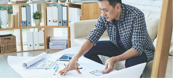 A man sits at a desk while looking at blueprints