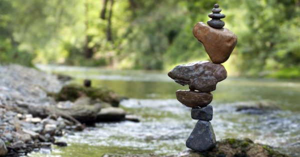 A cairn of rocks sits in the middle of a stream