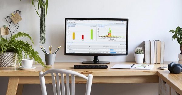 A home office set up with a laptop open to work management platform